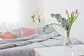 tulips in vase in cozy bedroom