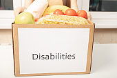 Charity and assistance to people in need. Women's hands hold a box of food products for Disabilities