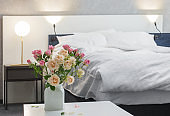 roses in vase on background bed in modern bedroom
