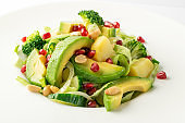 Green Salad with Avocado, Cucumber and Nuts on White Plate