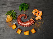 Grilled octopus tentacle on black stone plate served with shrimps
