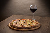 """Photo of Mozzarella cheese pizza with sliced """"u200b""""u200bred tomatoes. A glass of red wine to accompany. Gourmet photography done in horizontal.With spaces for texts"""