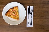 A delicious slice of mozzarella cheese pizza with slices of red tomatoes, served on a plate. Cutlery ready to be used. Gastronomic photography with space for texts.