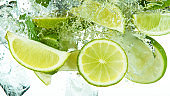 Lime Slices with ice cubes falling deeply under water