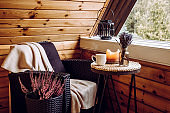Cute autumn hygge home decor arrangement. Tiny wooden cabin balcony with heather flowers in pot, lavender in bottle vase, candlelight flame, soft plaid waiting on comfortable garden furniture chair.