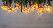 Star shape Christmas party lights hanging from upper section. Green spruce tree branches for decoration and red curled shiny strings. Lot of copy space.