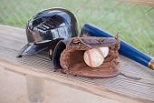 Baseball season is here.  Bat, glove, helmet and ball on dugout bench.