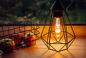 Modern black wire lamp with spiral light led bulb illuminated and wire basket next to it. Modern cozy interior with mood light.