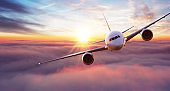 Commercial airplane flying above clouds in dramatic sunset light.