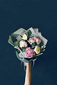 Bouquet of peonies with eucalyptus branches in hand