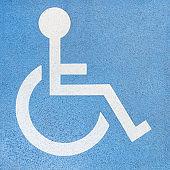Wheelchair user - white sign on blue concrete slab