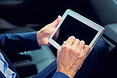 Businessman is using digital tablet in a car