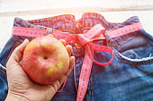 A woman's hand holds an Apple against the top of a pair of denim trousers on a wooden background. Blue jeans with a measuring tape instead of a belt. jeans with a measuring tape around the waist. The concept of a healthy lifestyle and diet.