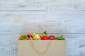 Vegetables in a brown paper bag on a white wood background
