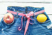 Top of denim trousers with Apple and lemon, on a wooden background. Blue jeans with a measuring tape instead of a belt. jeans with a measuring tape around the waist. The concept of a healthy lifestyle and diet.