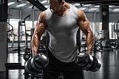 Muscular man with dumbbells in gym. Strong male bodybuilder working out