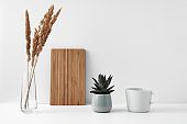 A mug, a potted houseplant, a clear vase and a wooden cutting board. Eco-friendly materials in the decor of the room, minimalism. Copy space, mock up.