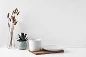 White cup and saucer on a wooden board, white background. Eco-materials and design. Copy space, mock up.
