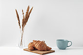 Blue mug and croissants on a white background. Eco-friendly and natural materials in the decor, dessert. Copy space, mock up.