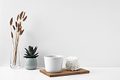 White mug and meringue cake on a white background. Eco-friendly and natural materials in decor and interior design, dessert. Copy space, mock up