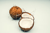 Parts of coconut on a colored background. Close up. Fresh ripe coconut broken into pieces.