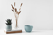 Mug and transparent vase with flowers on a white background. Eco-friendly materials in the decor of the room, minimalism. Copy space, mock up.