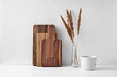 A mug, a transparent vase, and a wooden cutting board. Eco-friendly materials in the decor of the room, minimalism. Copy space, mock up.