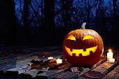 Halloween pumpkin burning in forest at night