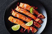 teriyaki salmon fillet baked in an oven served on a black plate with lime wedges on a concrete table