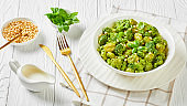 Italian gnocchi with broccoli florets tossed with basil pesto and creamy cheese sauce