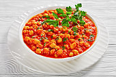Vegetarian dish: indian chana masala or chickpea curry with garam masala spices, tomato sauce, bay leaf,  sprinkled with parsley