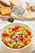 sweet corn salad with avocado, red onion slices and tomatoes