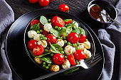 Summer salad of mini mozzarella balls, fresh baby spinach cherry tomatoes and young peas with balsamic vinegar dressing