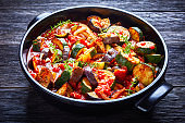 Stewed vegetables eggplant, tomatoes, zucchini with tomato sauce, garlic and herbs