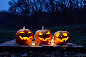 Halloween pumpkins burning in forest at night