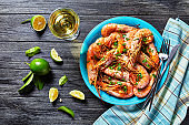 Garlic butter shrimps cooked on a skillet with lime and fresh parsley