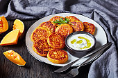 Leftover butternut squash fritters with tzatziki sauce on a plate with parsley