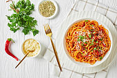 spaghetti with pork sausages ragout, tomatoes spices sprinkled with shredded parmesan cheese and chopped parsley in a white bowl