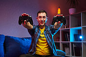 Portrait of crazy playful Gamer enjoying Playing Video Games indoors sitting on the sofa, holding Console Gamepad in hands. Resting At Home, have a great Weekend.