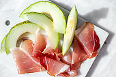 Jamon and melon on white marble background with copy space