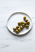 green olives on white marble background with copy space