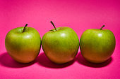 Green apple on pink background. Flat lay, top view, copy space . Food dietary concept.