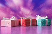 Three gift boxes  with reflection against holiday abstract background