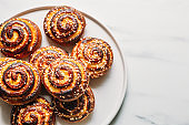 cottage cheese bun on marble background with copy space. Traditional finnish cinnamon rolls on the plate