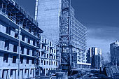 Crane and building construction site against blue sky, toned trendy classic blue color of year 2020