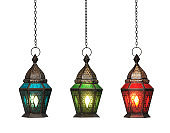 Ornamental Arabic lantern with burning candle glowing isolated on white background with clipping path
