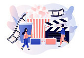 Online cinema. Mobile movie theater. Cinematography. Tiny people watching movie with popcorn,3d glasses and video attributes. Modern flat cartoon style. Vector illustration on white background