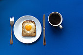 Breakfast concept. White plate with baked bread and egg and white coffee cup. Blue background.