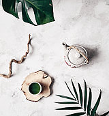 Matcha traditional Japanese powdered green tea in cup near teapot and plants during tea ceremony chado on white marble background