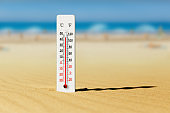 Sea coast at hot summer day. Wooden thermometer in the sand. Ambient temperature plus 45 degrees celsius